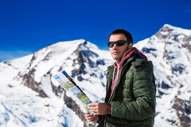 雪山の背景を楽しみにしている地図を持つ男グロースグロックナーオーストリア