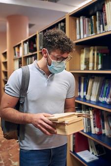 Человек с маской читает книги в университетской библиотеке