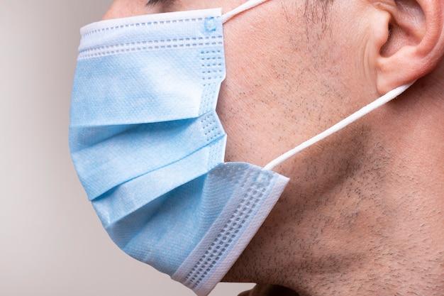 マスクを持つ男。医療用フェイスマスク。 covid-19、コロナウイルス。マスクを着用し、安全を確保してください。