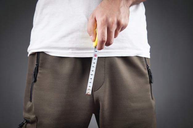 Мужчина с рулеткой измеряет размер своего члена.