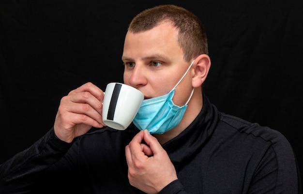 Человек с медицинской маской пьет кофе на темной стене