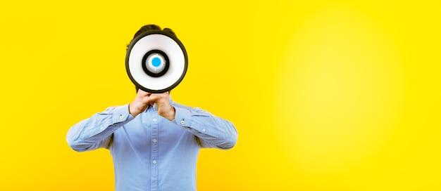 Человек с мегафоном на желтом фоне