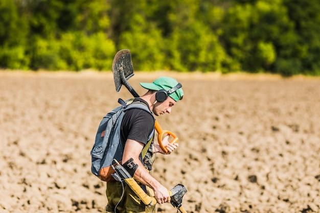 Человек с металлоискателем в поле. ищите сокровища.