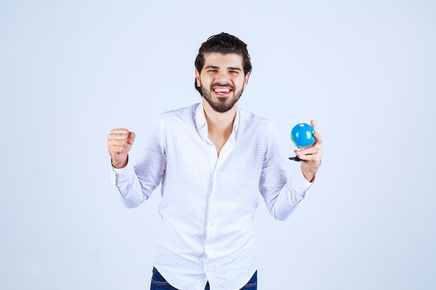 拳を見せているミニ地球儀を持つ男