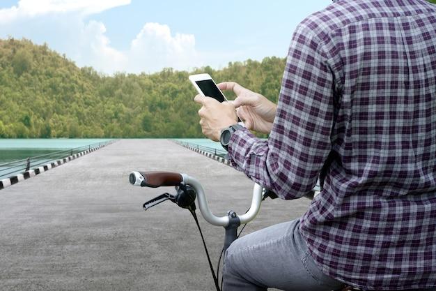 Человек с мобильным телефоном на велосипеде на улице