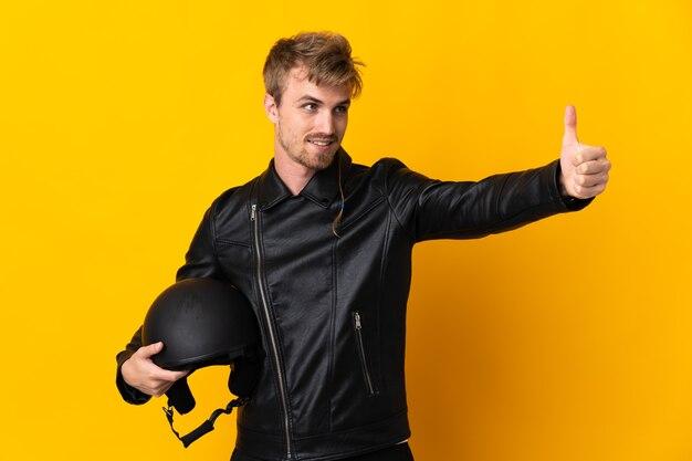 親指を立てるジェスチャーを与える孤立したオートバイのヘルメットを持つ男