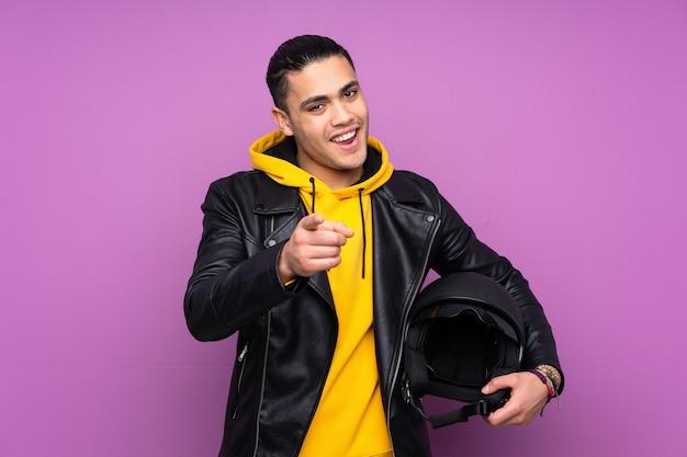 紫色の背景に分離されたオートバイのヘルメットを持つ男はあなたに指を指しています