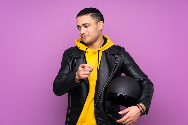 紫色の壁に分離されたオートバイのヘルメットを持つ男はあなたに指を指します