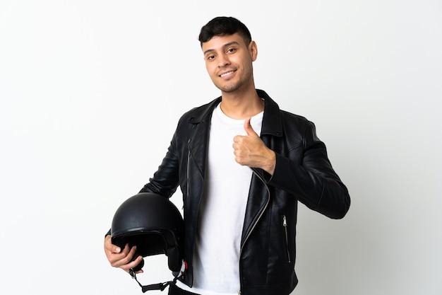 親指を立てるジェスチャーを与える白で隔離のオートバイのヘルメットを持つ男