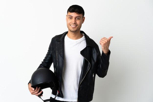 製品を提示する側を指している白で隔離のオートバイのヘルメットを持つ男