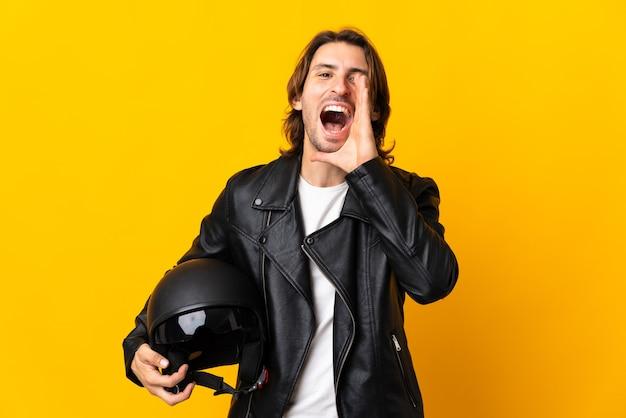 口を大きく開いて叫んで黄色の背景に分離されたオートバイのヘルメットを持つ男