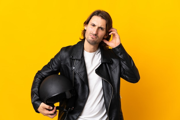 疑いを持って黄色に分離されたオートバイのヘルメットを持つ男