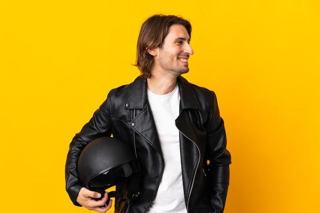 黄色に見える側に分離されたオートバイのヘルメットを持つ男