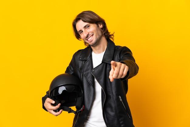 幸せな表情で黄色のポインティングフロントに分離されたオートバイのヘルメットを持つ男