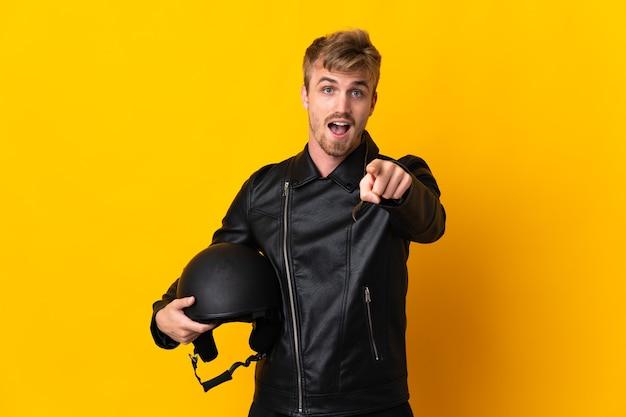 驚いて正面を向いている黄色で隔離のオートバイのヘルメットを持つ男