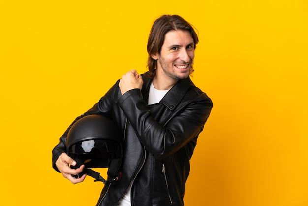 승리를 축하하는 노란색 벽에 고립 된 오토바이 헬멧을 가진 남자
