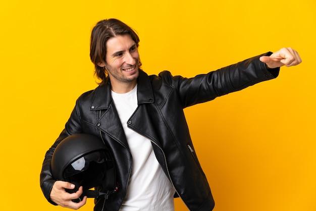 제스처를 엄지 손가락을주는 노란색 벽에 고립 된 오토바이 헬멧을 가진 남자