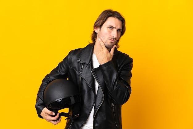 의심을 갖는 노란색 벽에 고립 된 오토바이 헬멧을 가진 남자