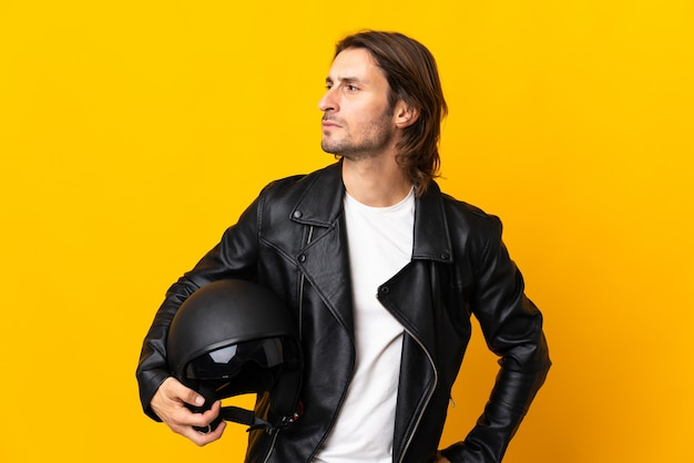 측면을 찾고 노란색 벽에 고립 된 오토바이 헬멧을 가진 남자