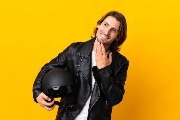 웃는 동안 찾고 노란색 벽에 고립 된 오토바이 헬멧을 가진 남자