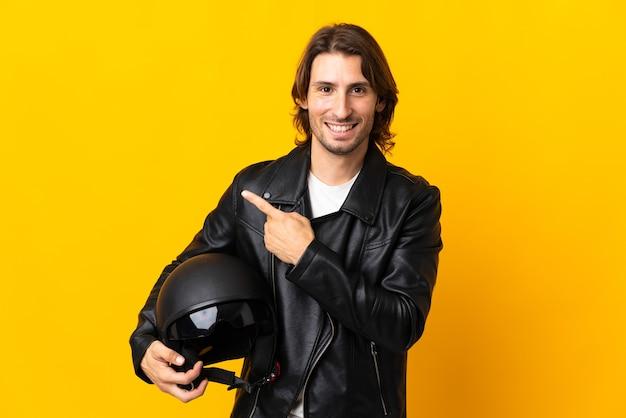 製品を提示する側を指している黄色の壁に分離されたオートバイのヘルメットを持つ男