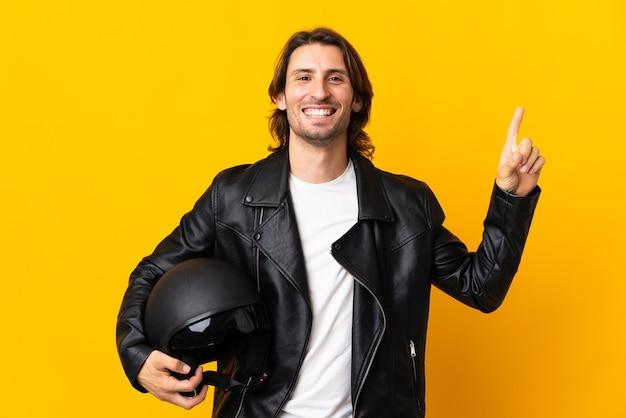 좋은 아이디어를 가리키는 노란색 벽에 고립 된 오토바이 헬멧을 가진 남자