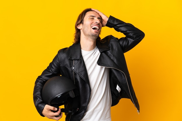 많이 웃 고 노란색 벽에 고립 된 오토바이 헬멧을 가진 남자