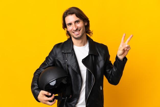 笑顔と勝利のサインを示す黄色の壁に分離されたオートバイのヘルメットを持つ男