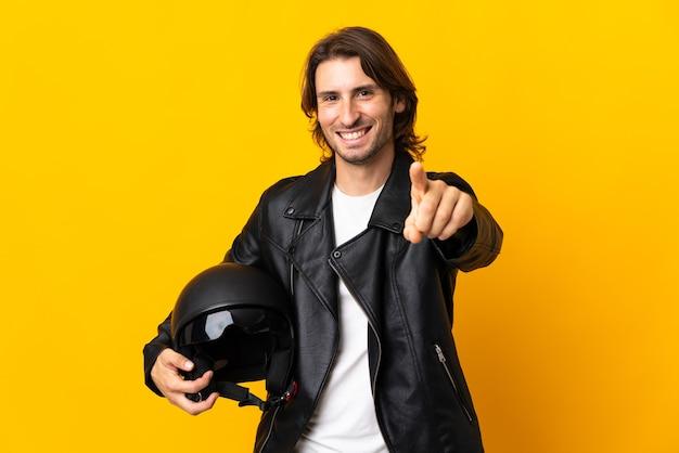 노란색 벽 놀라게 하 고 앞을 가리키는에 고립 된 오토바이 헬멧을 가진 남자