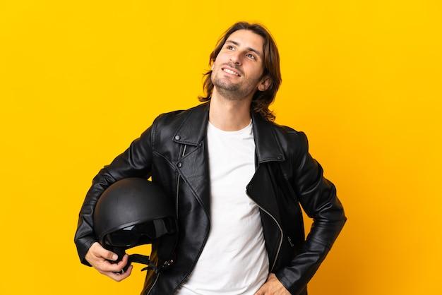 찾는 동안 아이디어를 생각 노란색 벽에 고립 된 오토바이 헬멧을 가진 남자