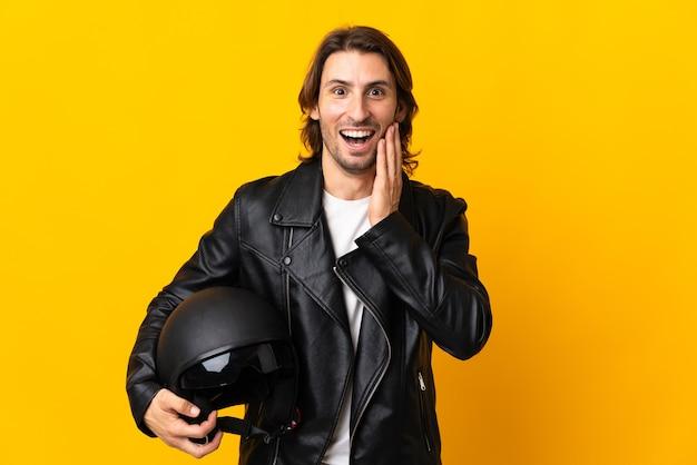 놀람과 충격 된 표정으로 노란색 벽에 고립 된 오토바이 헬멧을 가진 남자