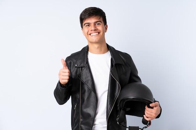 親指のジェスチャーを与える分離された青の上のオートバイのヘルメットを持つ男