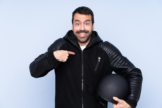 Человек с мотоциклетным шлемом над изолированной стеной с удивленным выражением лица