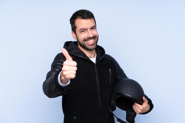 何か良いことが起こったので、親指で隔離された壁の上のオートバイのヘルメットを持つ男