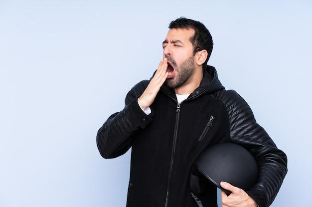 Человек с мотоциклетным шлемом над изолированной стеной, зевая и прикрывая широко открытый рот рукой