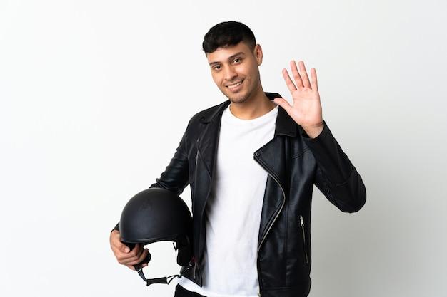 Человек в мотоциклетном шлеме салютует рукой со счастливым выражением лица