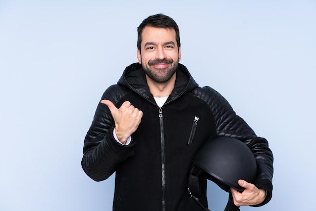 ジェスチャーと笑顔を親指でオートバイのヘルメットを持つ男