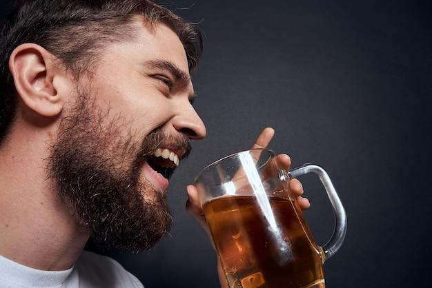Человек с кружкой пива в белой футболке эмоции образа жизни пьян на темном изолированном пространстве.