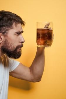 Мужчина с кружкой пива в белой футболке на желтом фоне