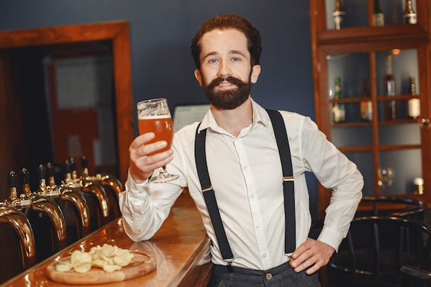 콧수염과 수염을 가진 남자가 술집에 서서 유리 잔으로 술을 마신다.