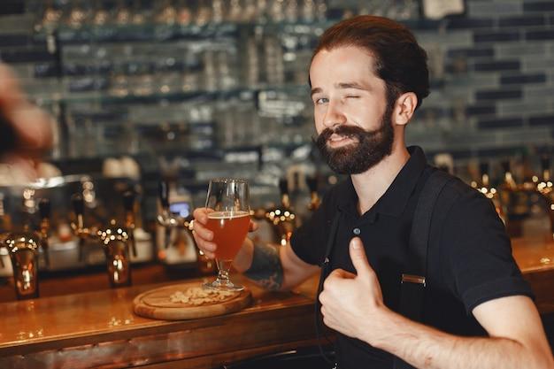 口ひげとあごひげを生やした男がバーに立ち、グラスからアルコールを飲みます。