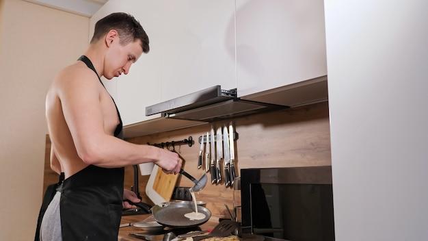 裸の胴体と黒いエプロンを着た男がキッチンでパンケーキを準備します。