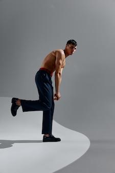 灰色の背景にジーンズと靴で裸の胴体を持つ男