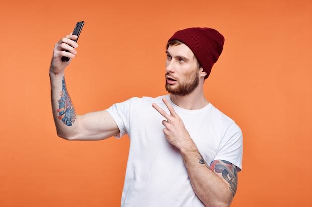 그의 손에 휴대 전화와 함께 남자 유행 모자 포즈 스튜디오