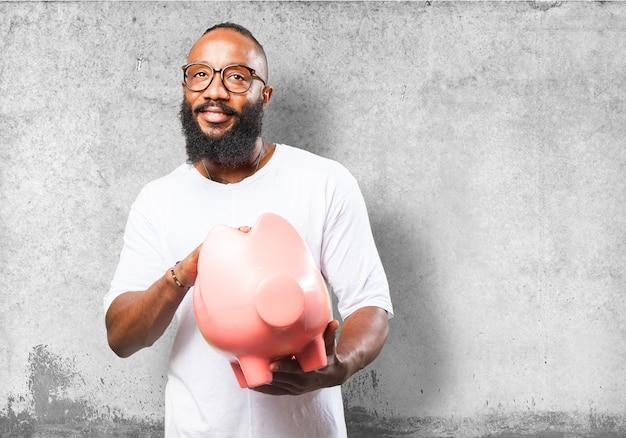 ピンクの豚の貯金箱を持つ男