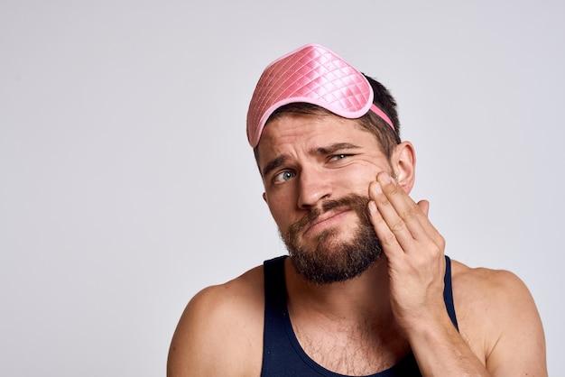 ピンクの睡眠マスクと灰色の背景のトリミングされたビューに黒のtシャツを持つ男。