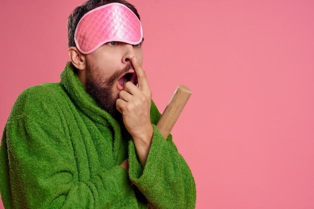 Человек с розовой маской для сна на лице в зеленом халате