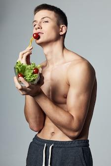 エネルギーライフスタイル孤立した背景のトレーニングを食べるサラダのプレートを持つ男