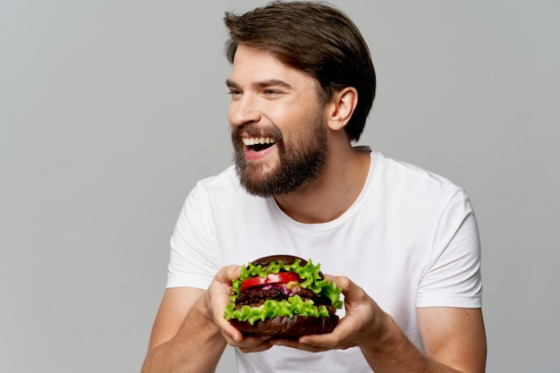 サラダのプレートを持つ男は笑って、灰色の背景で横に見えます