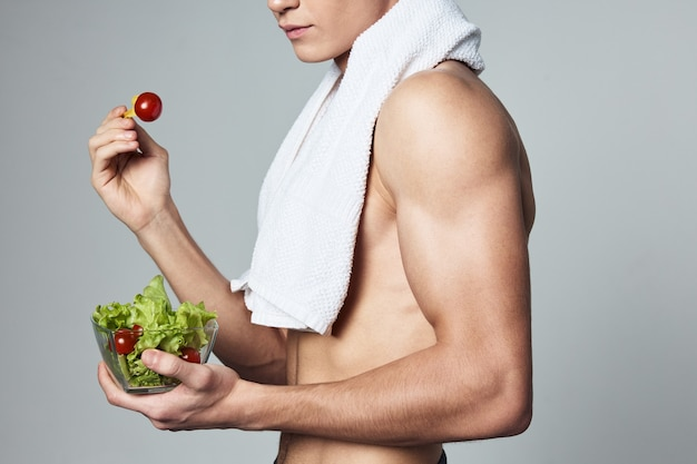 サラダの健康食品のトリミングされたビューの彼の肩のプレートにポンプアップされた体を持つ男